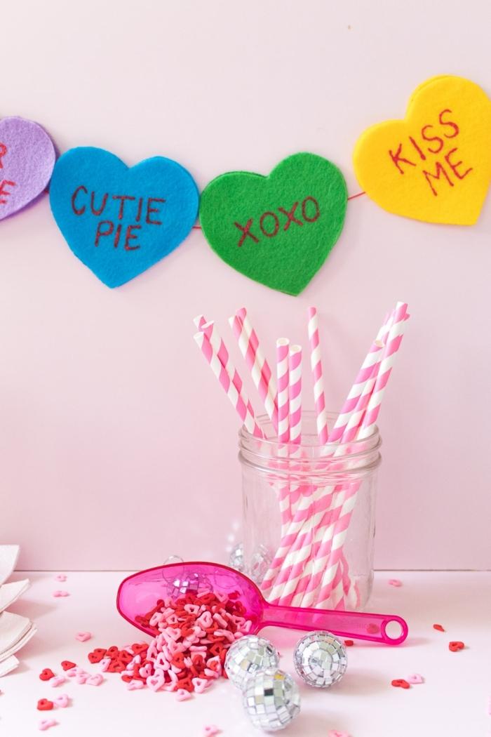 manualidades con tela, guirnalda de corazones de fieltro en diferentes colores con mensajes amorosos, decoración para San Valentin