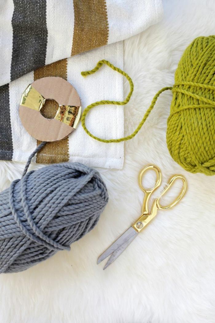 como hacer pompones de lana, materiales necesarios, hilo en gris y verde, tijeras, manta de diseño sencillo