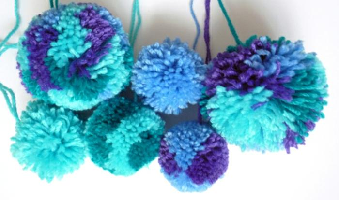 pompones de lana divertidos hechos de hilo en azul, verde y morado, manualdiades con lana fáciles de hacer
