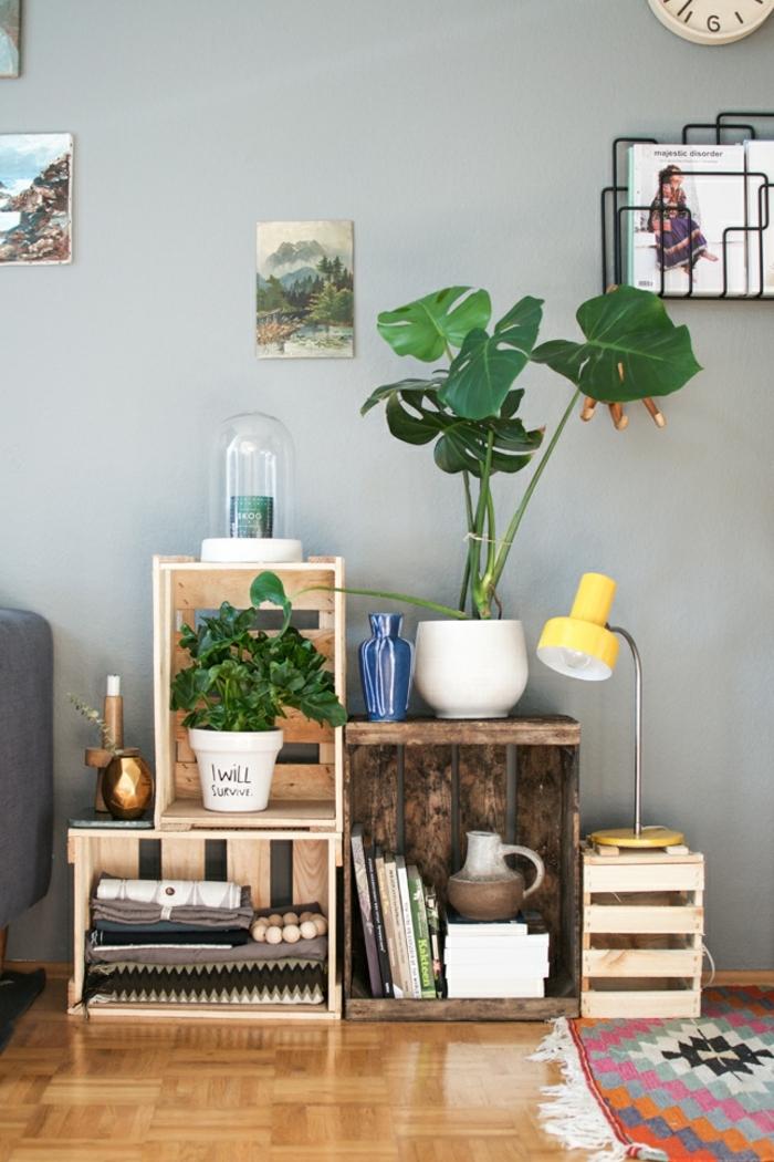 interior moderno con muchas plantas verdes, paredes en gris y suelo de parqueta, cajas de madera decoradas para hacer una estantería