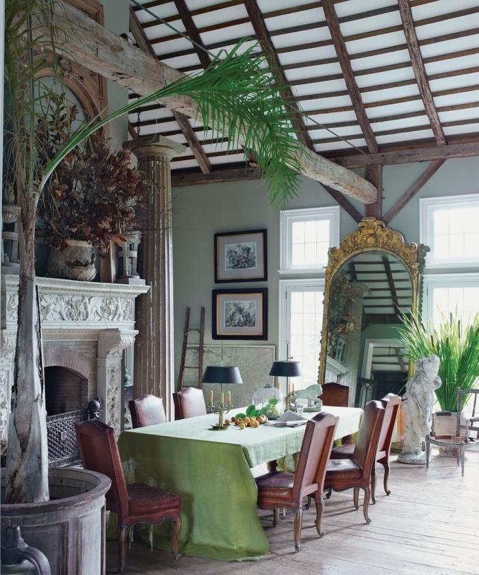 interior de encanto con muchos muebles y objeto en estilo vintage, comedor abuhardilldo con techo muy alto, decoración con espejos con marcos dorados