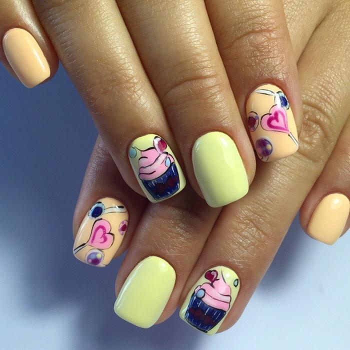 dibujos de encanto en las uñas, uñas decoradas pintadas en dos tonos del gama amarillo con dibujos de magdalenas y chupachups en forma de corazón