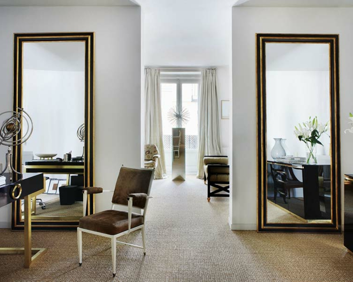 dos espejos muy grandes con marcos en dorado y negro, decoración con espejos para salones, suelo con moqueta y silla tapizada
