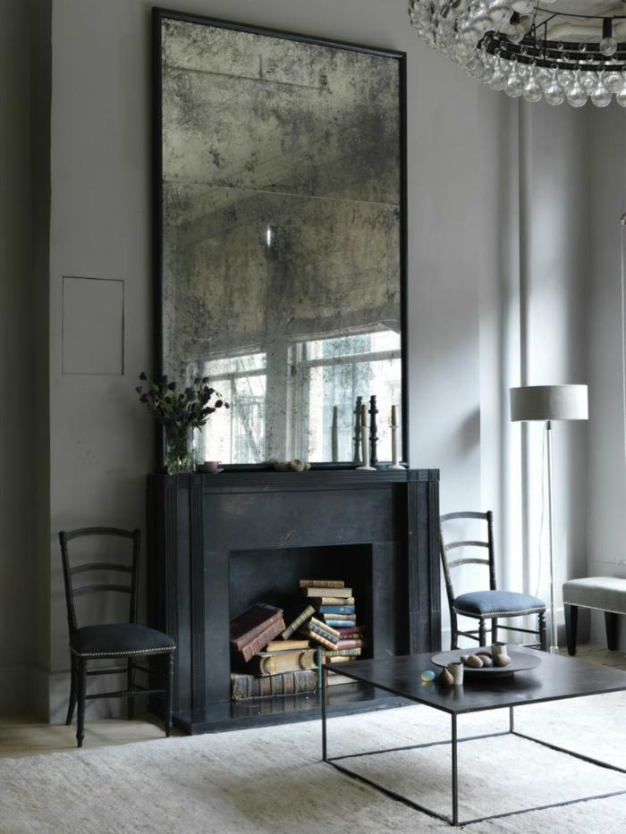 espejo muy grande en estilo vintage, chimenea antigua en negro con libros antiguos, interior en gris y negro