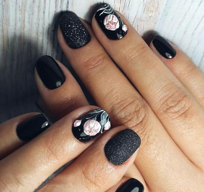 ideas de diseños de uñas con motivos florales, flores en rosado en fondo negro, dedo pulgar con gel purpurina acabado mate