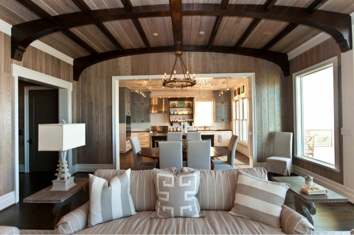 como decorar espacios abiertos, cocinas abiertas al salon en colores claros y terrosos, techo con vigas de madera, cojines decorativos