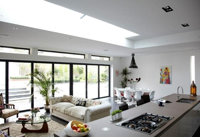 cocinas abiertas al salon con encanto y mucha luz, espacio decorado en blanco con grande barra, sofá beige en capitoné, decoración de plantas verdes