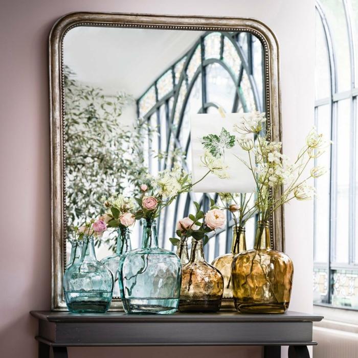 recibidores pequeños decorados de grandes espejos y flores, jarrones de diseño original con rosas, pared en color rosa