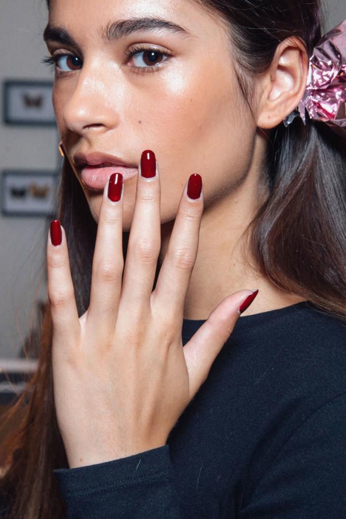 tendencias en diseños de uñas, uñas largas pintadas en rojo bordeos, forma ovalada, mujer con pelo castaño largo