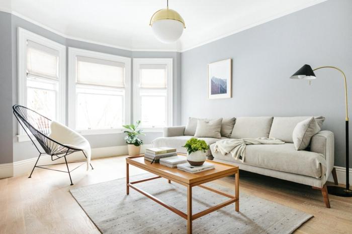luminoso salon decorado en colores claros con bonitos elementos arquitectónicos, paredes en gris y sofa en beige