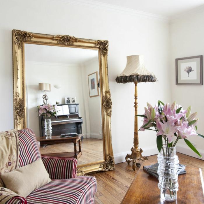 preciosa sala de estar con grande espejo dorado apoyado en la pared, decoración con espejos en estilo vintage y bonitas flores