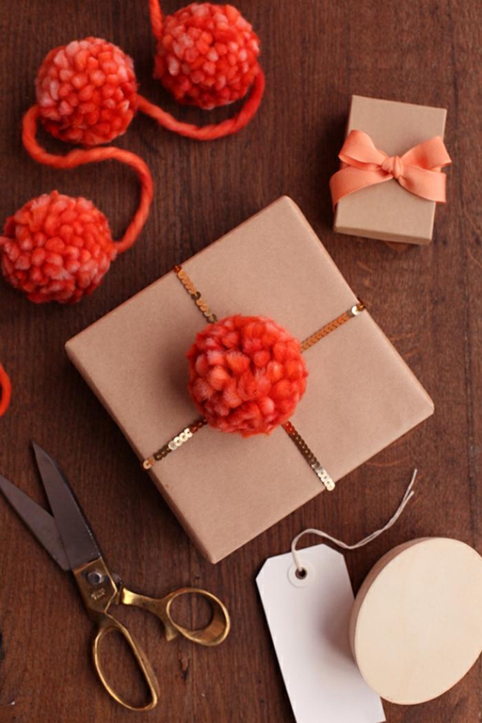 como empaquetar los regalos de Navidad de una manera original, manualidades con pompones de lana, hilo en color rojo fuego