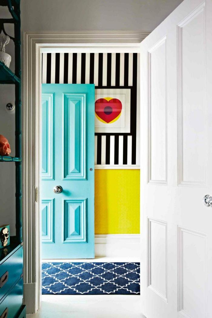 recibidores pequeños de encanto, entrada en colores llamativos, puerta en color aguamarina, pared con papel pintado en rayas en blanco y negro