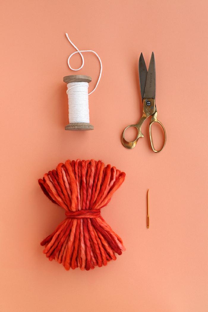 hilo de lana en rojo y naranja, hilo blanco, tijeras y aguja, materiales necesarios para elaborar unos pompones de lana caseros