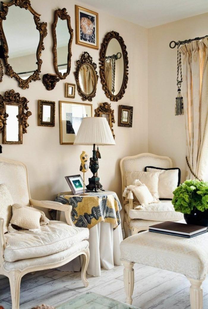 propuesta de decoración con espejos en un salón en estilo vintage, paredes en color crema, sillones grandes y muchos espejos
