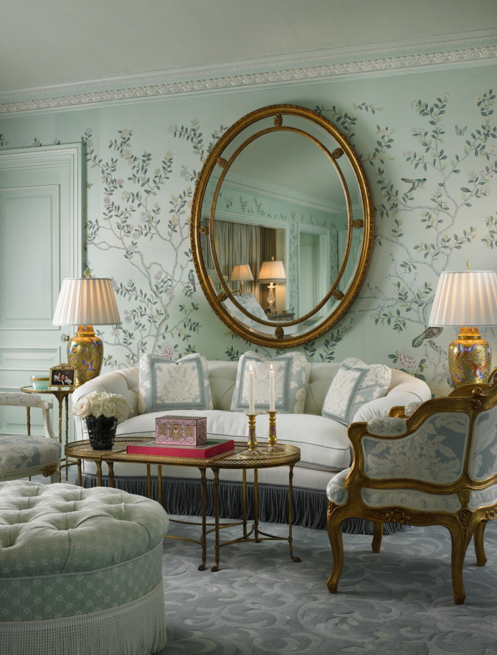 decoración con espejos para salones vintage, papel pintado en color verde menta con motivos florales, muebles tapizados en capitoné