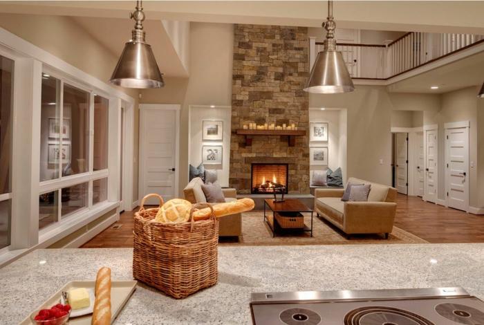 interior en colores calidos y claros, cocinas abiertas al salon de estilo moderno, barra grande funcional, sala de estar con chimenea de leña
