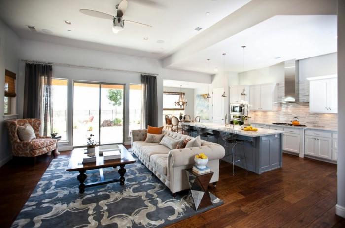 ejemplo de un piso con espacios abiertos, cocinas abiertas al salón con encanto, decoracion en blanco y gris, sofá en capitoné y alfombra ornamentada