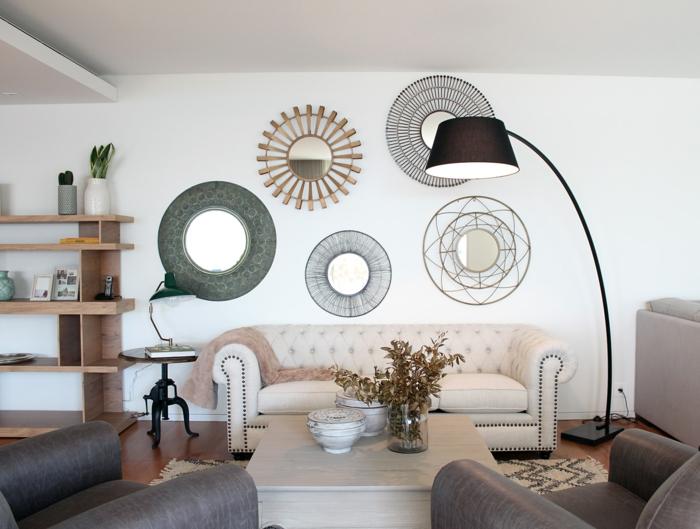 ejemplos de salones con decoración con espejos, varios espejos de forma oval con marcos diferentes, sofá en beige tapizada en capitoné