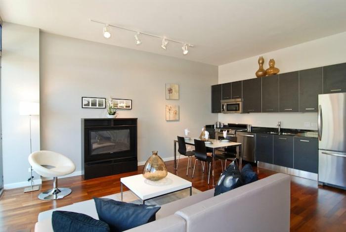 salon moderno en tonos claros con detalles en azul oscuro, sillas modernas, iluminacion con lamparas originales