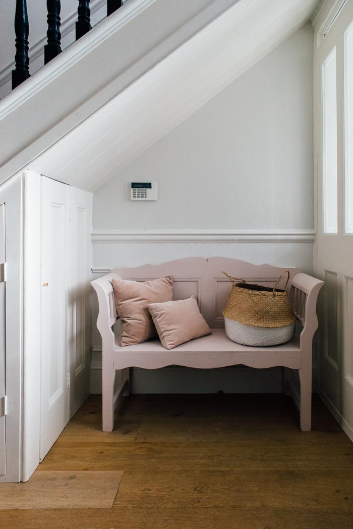 pequeños recibidores con un solo muebles, banco de época pintado en color rosa, cojines decorativos y cesta de mimbre