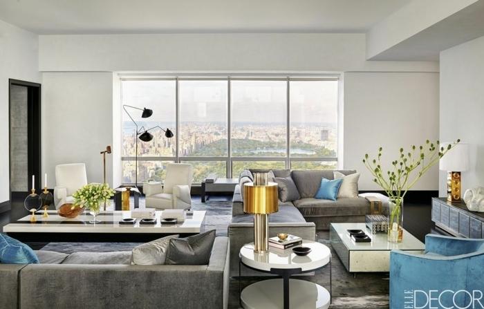 salon de encanto con grandes ventanales con vista, sofá en gris y sillón tapizado de terciopelo en azul