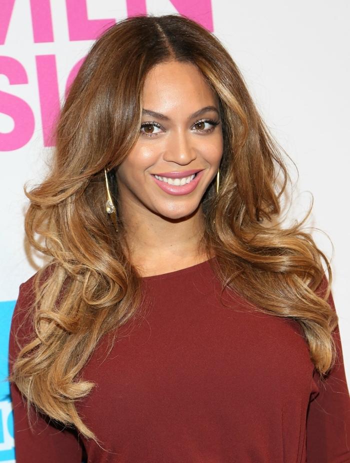 Beyonce con pelo suelto ondulado, peinado con mucho volumen, como escoger entre mechas californianas y balayage