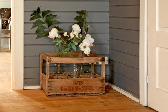 macetero DIY hecho de cajas de madera, bonitas flores en blanco, paredes en gris y suelo de parquet