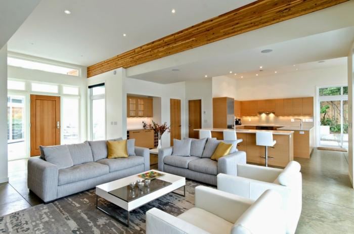 precioso ejemplo de cocina unida con el salon, cocinas abiertas al salón en tonos claros, decoracion con vigas de madera, sofás en gris y blanco