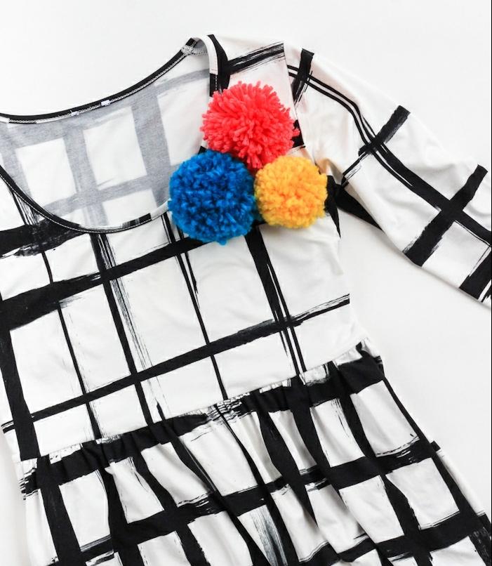 vestido con estampado en cuadros en blanco y negro y decoracion divertida de pompones, manualidades con pompones originales