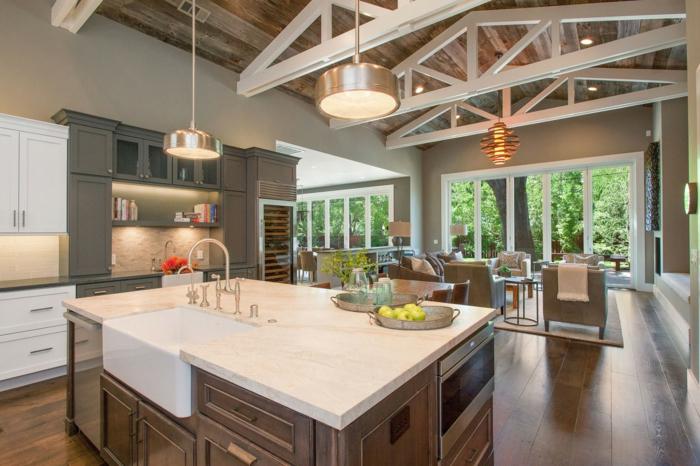 estancia agradable con aire hogareño, detalles en estilo rústico, techo con vigas de madera, cocinas abiertas al salón decoradas en blanco y marron