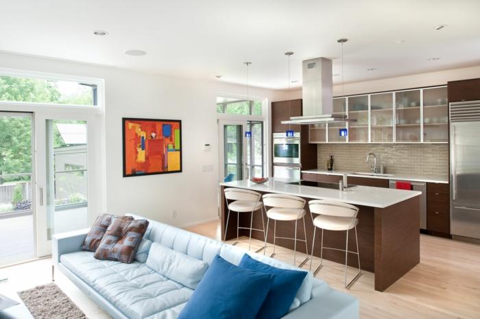 diseño de encanto de un salón abierto a la cocina americana, pintura impresionista en la pared, paredes en blanco, sofá en azul claro