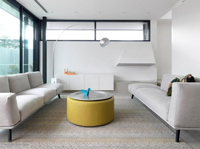 salon de forma cuadrada con dos sofás en color gris y pequeña mesa redonda en color mostaza, decoracion salon moderno en colores claros