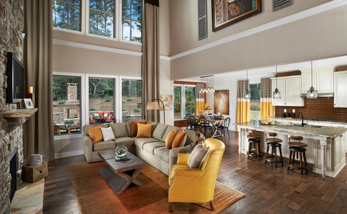 estancia con techo muy alto y grandes ventanales, cocina americana abierta al salón, muebles en color beige y mostaza