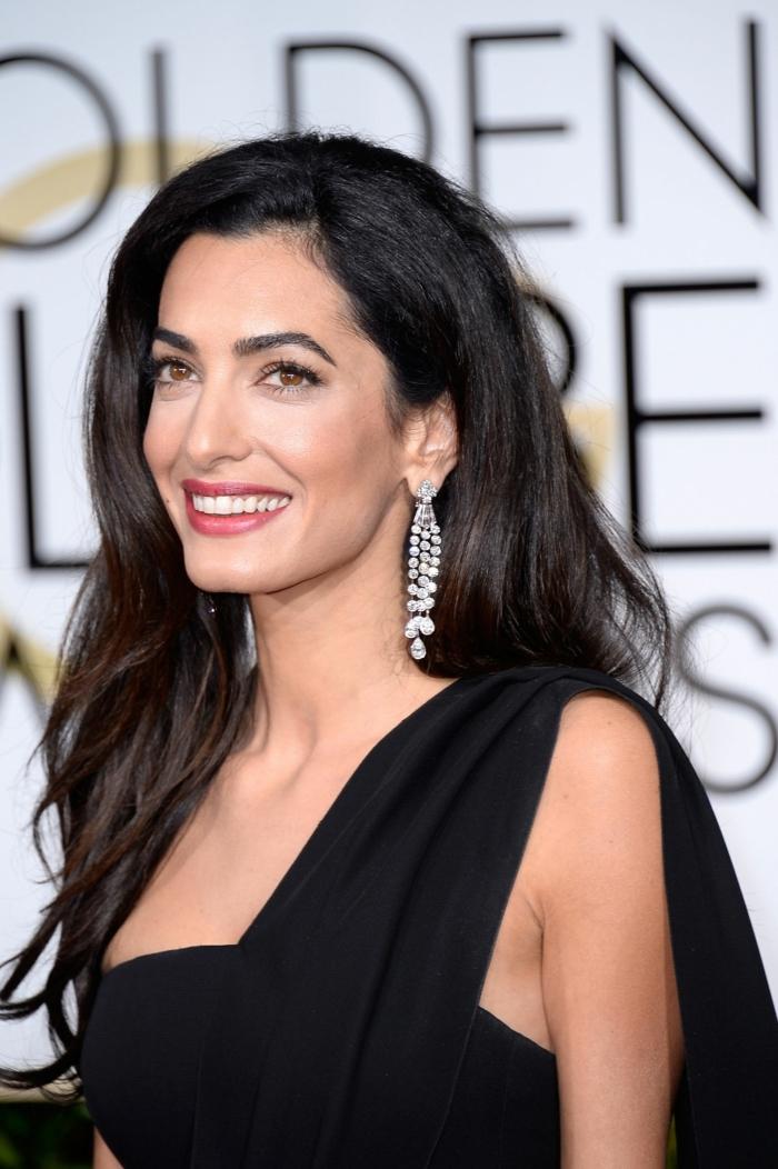 melenas largas oscuras con balayage, Amal Clooney con un vestido negro asimétrico y pendientes largas, pelo ligeramente ondulado, mechas balayage negro y castaño chocolate