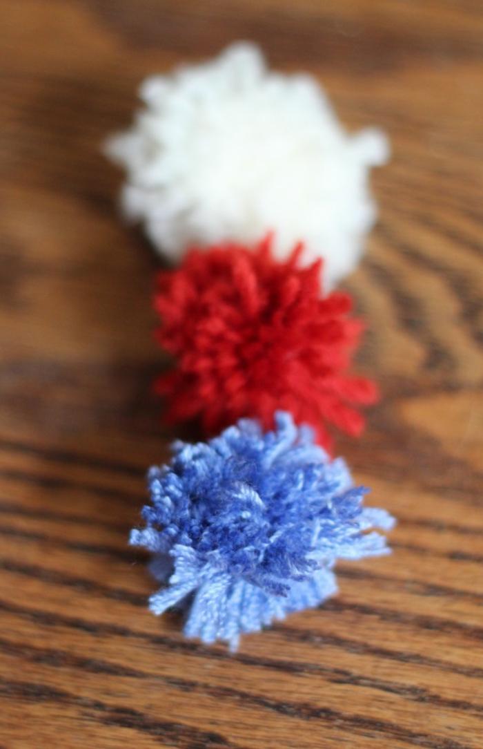tres bolas peludas de lana en blanco, rojo y azul porcelana, manualidades con pompones para decorar el hogar en Navidad