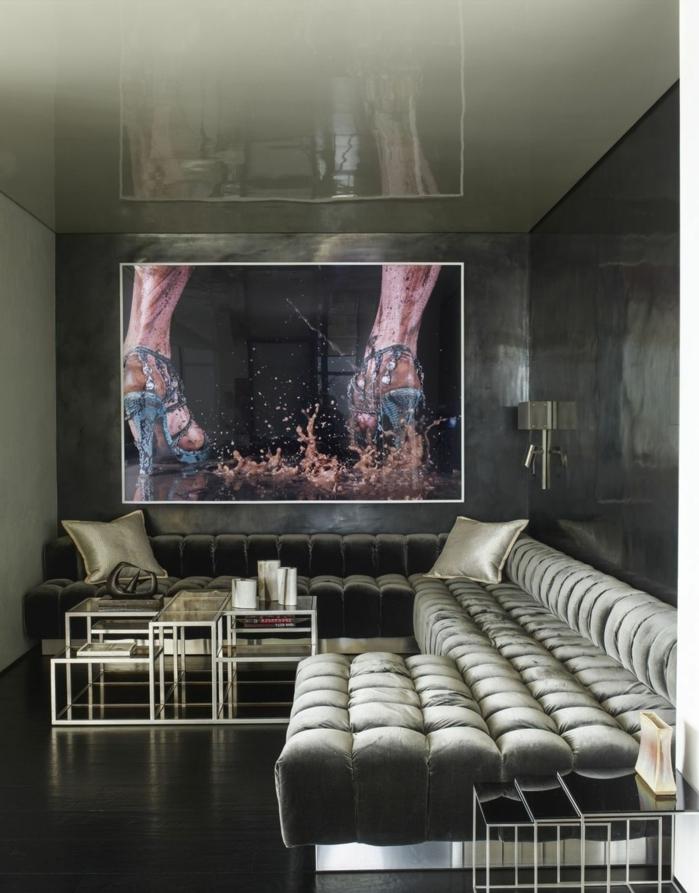 diseño de interiores moderno en colores oscuros con preciosa sofá en capitoné, mesa moderna de metal