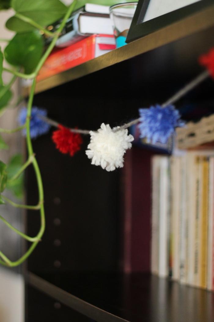 motivos navideños para decorar la casa, guirnalda de navidad hecha de pompones caseros, manualidades con pompones faciles de hacer