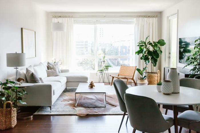 salon con decoracion de plantas verdes, sofa en color champán, comedor pequeño con mesa oval y suelo de parquet