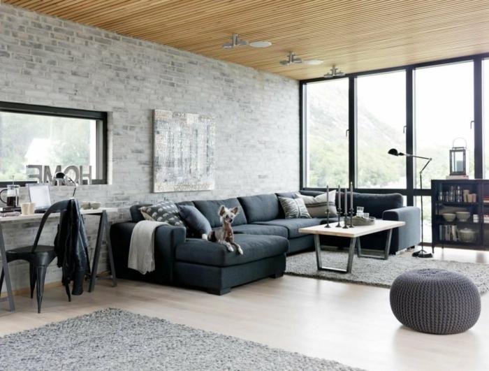 diseño espectacular de un salon con grandes ventanales y paredes de ladrillo, decoracion salon moderno con techo de madera y sofá en gris oscuro