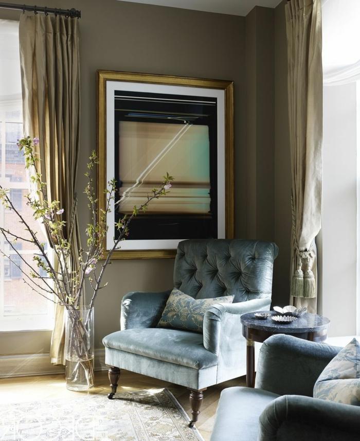 bonita combinación de ocre y gris, sillones elegantes tapizados en capitoné, decoracion salon moderno con paredes en beige y cortinas en dorado