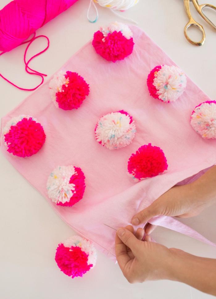 como hacer pompones con lana paso a paso, bolso en color rosa decorado con grandes bolas de hilo DIY