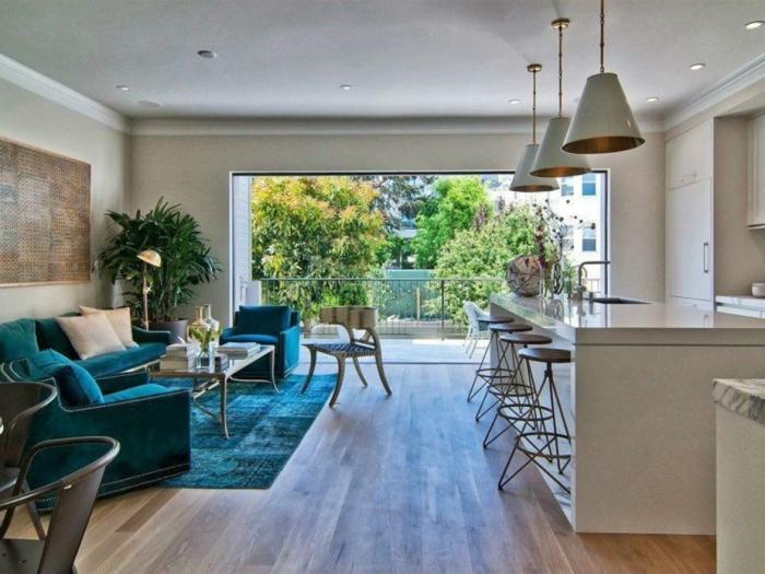 diseño de salon comedor, sillones y sofá tapizados en color aguamarina, cocina en blanco con grande barra, grande ventanal con vista