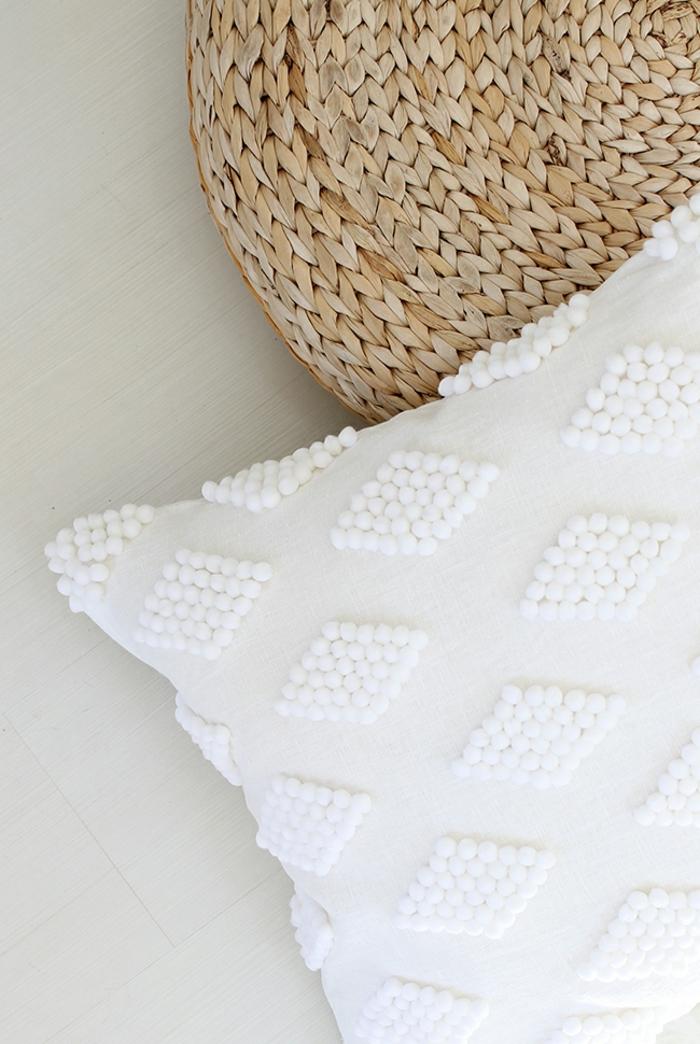 cojín blanco decorado con pequeños pompones en blanco, como hacer pompones con lana paso a paso, manualidades útiles