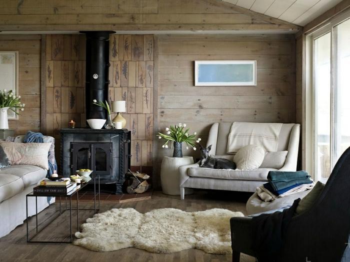 muebles estilo nordico, salón con chimenea de metal negra, paredes de listones, tapete beige peludo, mesa baja de metal y vidrio con revistas, sillón con perrito, ventana grande
