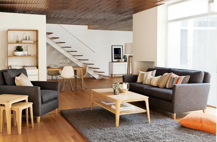 casas nordicas, salón comedor con escaleras, decoración en gris y madera clara, tapete peludo, ventana con persianas, comedor con velas y sillas de plástico, techo de listones