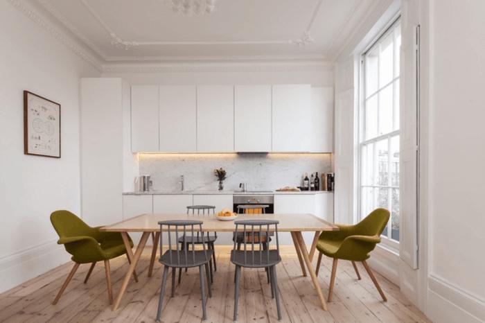 cocina comedor con ventana grande, casas nordicas, suelo con tarima, mesa grande rectangular, sillas de madera gris y sillas tapizadas color oliva, decoración minimalista