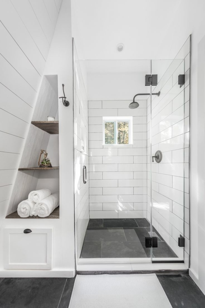 ducha de obra con ventana pequeña y puerta de vidrio, ideas baños pequeños, ambiente con pared inclinada, nicho con estantes, decoracion en blanco y negro