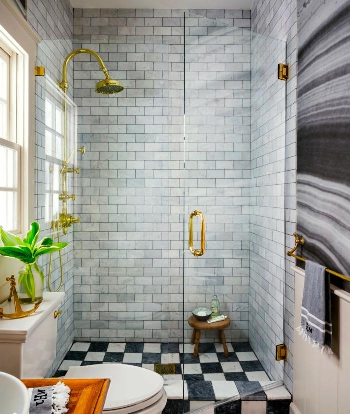 ideas baños pequeños, baño con mucha luz natural, ducha dorada, puerta y mámpara de vidrio, baldosas de diferente tamaño, suelo con efecto tablero de ajedrez