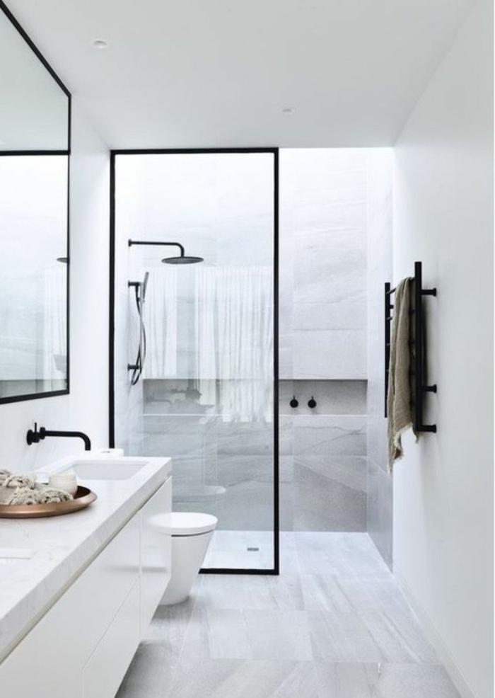 cuarto de baño largo y estrecho, decoracion baños pequeños, marmol, lavabo doble, mampara de vidrio, toallero negro, pared con nicho